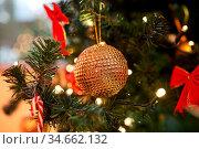 golden christmas ball decoration on fir tree. Стоковое фото, фотограф Syda Productions / Фотобанк Лори
