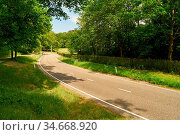 Zweispurige Straße mit Kurve im Sommer durch grüne Natur. Стоковое фото, фотограф Zoonar.com/Robert Kneschke / age Fotostock / Фотобанк Лори