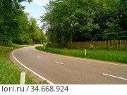 Leere Landstraße mit Kurve im Sommer durch eine grüne Landschaft. Стоковое фото, фотограф Zoonar.com/Robert Kneschke / age Fotostock / Фотобанк Лори