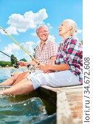 Glückliches Senioren Paar hat Spaß zusammen beim Angeln am See im... Стоковое фото, фотограф Zoonar.com/Robert Kneschke / age Fotostock / Фотобанк Лори
