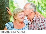 Verliebter Senior gibt seiner Freundin einen Kuss in der Natur im... Стоковое фото, фотограф Zoonar.com/Robert Kneschke / age Fotostock / Фотобанк Лори
