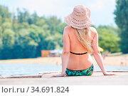 Junge Frau genießt die Sonne auf einem Steg am Meer oder Badesee ... Стоковое фото, фотограф Zoonar.com/Robert Kneschke / age Fotostock / Фотобанк Лори