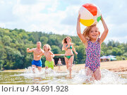 Kleines Mädchen läuft mit einem Ball im Meer in den Sommerferien ... Стоковое фото, фотограф Zoonar.com/Robert Kneschke / age Fotostock / Фотобанк Лори