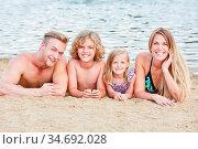 Familie mit zwei Kindern entspannt sich am Strand am Meer im Sonnenschein. Стоковое фото, фотограф Zoonar.com/Robert Kneschke / age Fotostock / Фотобанк Лори