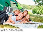 Glückliche Familie beim Camping im Zelt macht ein Selfie Foto mit... Стоковое фото, фотограф Zoonar.com/Robert Kneschke / age Fotostock / Фотобанк Лори