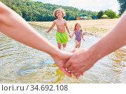 Eltern halten sich an den Händen im Sommerurlaub mit ihren Kindern... Стоковое фото, фотограф Zoonar.com/Robert Kneschke / age Fotostock / Фотобанк Лори