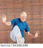 Alter lächelnder Mann bleibt aktiv im Fitnesscenter durch Bewegung. Стоковое фото, фотограф Zoonar.com/Robert Kneschke / age Fotostock / Фотобанк Лори