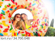 Girls with kiss expression and inflatable doughnut. Стоковое фото, фотограф Сергей Новиков / Фотобанк Лори