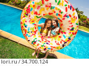 Two girls with inflatable doughnut near pool. Стоковое фото, фотограф Сергей Новиков / Фотобанк Лори