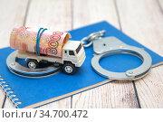Детская машинка, деньги и наручники. Нелегальные грузоперевозки. Стоковое фото, фотограф Наталья Осипова / Фотобанк Лори