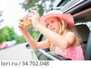Mädchen im Auto macht ein Selfie Foto aus dem Seitenfenster während... Стоковое фото, фотограф Zoonar.com/Robert Kneschke / age Fotostock / Фотобанк Лори