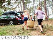 Zwei Kinder laufen mit einer Tasche zum Auto vor der Reise in den... Стоковое фото, фотограф Zoonar.com/Robert Kneschke / age Fotostock / Фотобанк Лори