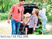 Sohn hilft Vater beim Tragen von Gepäck vor der Reise in den Sommerurlaub. Стоковое фото, фотограф Zoonar.com/Robert Kneschke / age Fotostock / Фотобанк Лори
