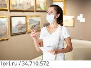 Woman in mask observing artworks in museum. Стоковое фото, фотограф Яков Филимонов / Фотобанк Лори