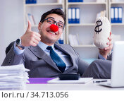 Clown businessman in the office with the a money sack. Стоковое фото, фотограф Elnur / Фотобанк Лори