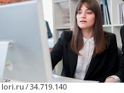 Business woman sitting in front of computer and looking at its screen. Стоковое фото, фотограф Zoonar.com/Ivan Mikhaylov / easy Fotostock / Фотобанк Лори