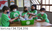 Group of kids wearing face masks putting plastic items in recycle container. Стоковое видео, агентство Wavebreak Media / Фотобанк Лори