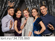 friends with microphone singing at christmas party. Стоковое фото, фотограф Syda Productions / Фотобанк Лори