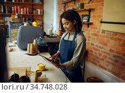 Female barista in apron take orders in cafe. Стоковое фото, фотограф Tryapitsyn Sergiy / Фотобанк Лори