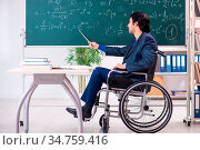 Young handsome man in wheelchair in front of chalkboard. Стоковое фото, фотограф Zoonar.com/Elnur Amikishiyev / easy Fotostock / Фотобанк Лори