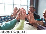 Business people's palms clasped together, giving high five to each... Стоковое фото, фотограф Zoonar.com/Tatiana Badaeva / easy Fotostock / Фотобанк Лори