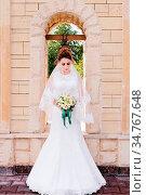 A beautiful bride in a wedding dress and a wedding bouquet in her... Стоковое фото, фотограф Zoonar.com/Ian Iankovskii / easy Fotostock / Фотобанк Лори