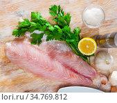 Perch fillet on cutting board with lemon and parsley. Стоковое фото, фотограф Яков Филимонов / Фотобанк Лори