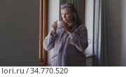 Woman drinking coffee while looking out of the window at home. Стоковое видео, агентство Wavebreak Media / Фотобанк Лори