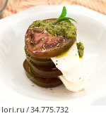 caprese salad with mozzarella, black tomatoes and pesto in white plate. Стоковое фото, фотограф Татьяна Яцевич / Фотобанк Лори