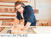 Junger Schreiner oder Tischler sägt Holz mit einer Kreissäge in der... Стоковое фото, фотограф Zoonar.com/Robert Kneschke / age Fotostock / Фотобанк Лори