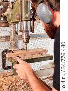 Schreiner oder Tischler bohrt ein Loch in ein Holz Brett mit einer... Стоковое фото, фотограф Zoonar.com/Robert Kneschke / age Fotostock / Фотобанк Лори