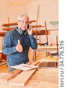 Älterer Handwerker hält den Daumen hoch beim Telefonieren mit dem... Стоковое фото, фотограф Zoonar.com/Robert Kneschke / age Fotostock / Фотобанк Лори