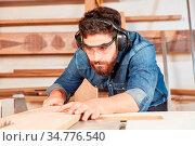 Mann als Schreiner in der Werkstatt sägt konzentriert Holz mit der... Стоковое фото, фотограф Zoonar.com/Robert Kneschke / age Fotostock / Фотобанк Лори