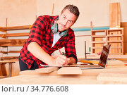 Mann als erfolgreicher Handwerker macht sich Notizen in der Schreinerei... Стоковое фото, фотограф Zoonar.com/Robert Kneschke / age Fotostock / Фотобанк Лори