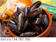 Delicious baked mussels on a bowl with onion sauce at table. Стоковое фото, фотограф Яков Филимонов / Фотобанк Лори