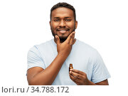 african man applying grooming oil to beard. Стоковое фото, фотограф Syda Productions / Фотобанк Лори
