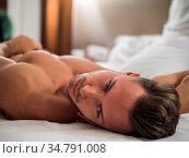 Shirtless sexy male model lying alone on his bed in his bedroom, looking... Стоковое фото, фотограф Zoonar.com/Stefano Cavoretto / easy Fotostock / Фотобанк Лори