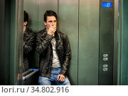 Scared young man desperate in stuck elevator screaming, looking very... Стоковое фото, фотограф Zoonar.com/STEFANO CAVORETTO / easy Fotostock / Фотобанк Лори