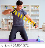 Young man exercising at home in sports and healthy lifestyle concept. Стоковое фото, фотограф Zoonar.com/Elnur Amikishiyev / easy Fotostock / Фотобанк Лори