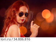 Serious girl in red bra with gun on background with blurred lights... Стоковое фото, фотограф Zoonar.com/A.Tugolukov / easy Fotostock / Фотобанк Лори