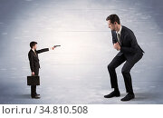 Tiny businessman with gun shooting giant fearful businessman. Стоковое фото, фотограф Zoonar.com/ranczandras / easy Fotostock / Фотобанк Лори