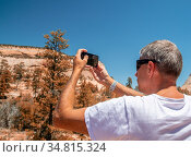Back view of male tourist in t-shirt taking pictures of national park... Стоковое фото, фотограф Giovanni Gagliardi / easy Fotostock / Фотобанк Лори