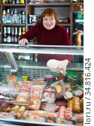 Cheerful selling sausage and ham at the counter. Стоковое фото, фотограф Яков Филимонов / Фотобанк Лори