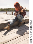 Red haired teen girl sings a song with ukulele. Стоковое фото, фотограф EugeneSergeev / Фотобанк Лори