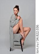 Beautiful barefoot woman in cardigan. She is sitting on high chair... Стоковое фото, фотограф Zoonar.com/© Dmitry Raikin / easy Fotostock / Фотобанк Лори