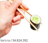 Female hand with disposable chopsticks holds kappa maki sushi roll... Стоковое фото, фотограф Zoonar.com/Valery Voennyy / easy Fotostock / Фотобанк Лори