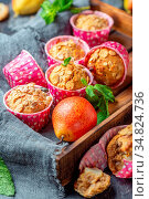 Muffins with muesli and ripe pears in a wooden tray with linen cloth... Стоковое фото, фотограф Zoonar.com/Marina Saprunova / easy Fotostock / Фотобанк Лори