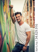 Attractive muscle man leaning on colorful graffiti wall, wearing white... Стоковое фото, фотограф Zoonar.com/STEFANO CAVORETTO / easy Fotostock / Фотобанк Лори