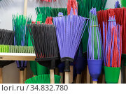 Sale of household goods, cleaning equipment for the house plastic broom brushes with a wooden handle different in the store on the showcase. Стоковое фото, фотограф Светлана Евграфова / Фотобанк Лори