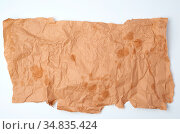 Torn crumpled piece of brown paper with grease stains on a white background... Стоковое фото, фотограф Zoonar.com/Danko Natalya / easy Fotostock / Фотобанк Лори
